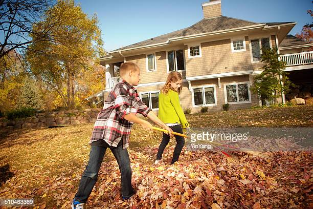Children Helping Rake Leaves in Backyard