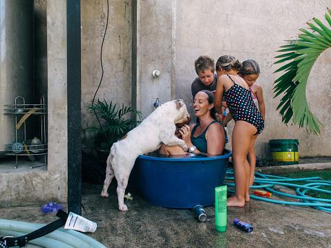 Children helping woman bathe in plastic tub - gettyimageskorea