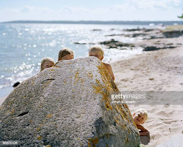 Children hiding behind a large rock on a beach Sweden.
