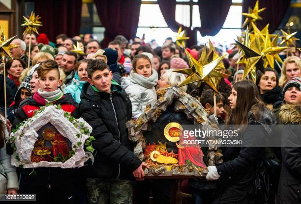 Children hold a nativity scene diorama and sing church songs on Christmas eve during a religious service to celebrate Orthodox Christmas in St...