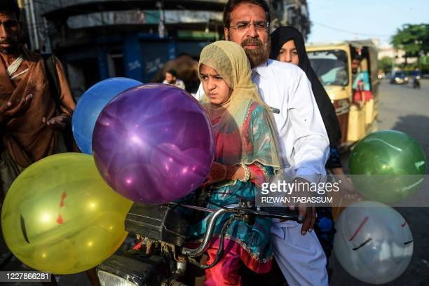 Children hold balloons after offering prayers with their father during the Eid al-Adha, the feast of sacrifice, in Karachi on August 1, 2020.