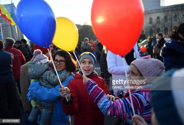 Children hold baloons in the colours of the Romanian flag as people protest in front of the government headquarters against the government's...