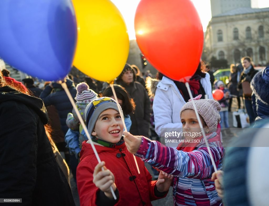 Children hold baloons in the colours of the Romanian flag as people protest in front of the government headquarters against the government's contentious corruption decree in Bucharest, Romania on February 5, 2017. Romania's government formally repealed contentious corruption legislation that has sparked the biggest protests since the fall of dictator Nicolae Ceausescu in 1989, ministerial sources said. The emergency decree, announced on Tuesday (January 31, 2017), would have decriminalised certain corruption offences, raising concerns in Romania and outside that the government was easing up on fighting graft. Centre-right President Klaus Iohannis, elected in 2014 on an anti-graft platform, previously had called the decree 'scandalous' and moved to invoke the constitutional court. / AFP / Daniel MIHAILESCU