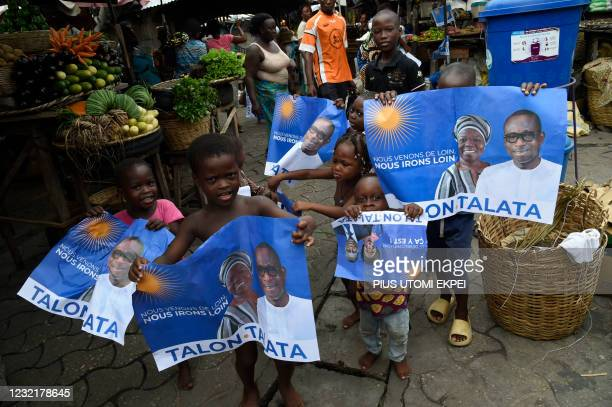 Children hold campaign posters with photographs of incumbent Benin President Patrice Talon and running mate Mariam Talata at the market in Cotonou on...