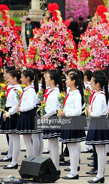 Children hold flowers to present to the monument of People's heroes during the commemoration ceremony for the first Martyrs' Day at the People's...