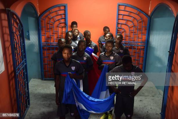 Children hold national flags of Haiti and Nicaragua before the match at the Sylvio Cator Stadium in PortauPrince on March 24 the first of two match...