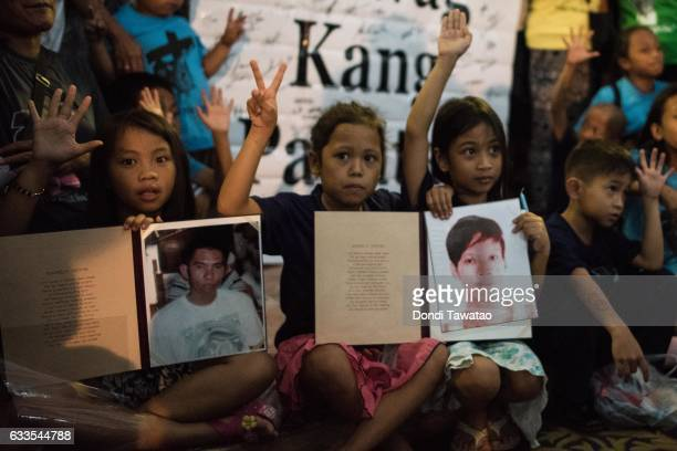 Children hold pictures of their loved ones killed during a mass held for victims of the drug war on February 2 2017 in Manila Philippines Philippine...