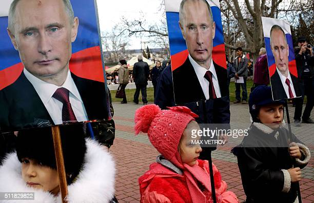 Children hold portraits of Russia's President Vladimir Putin as they take part in a rally to mark Defender of the Fatherland Day in the Crimean city...