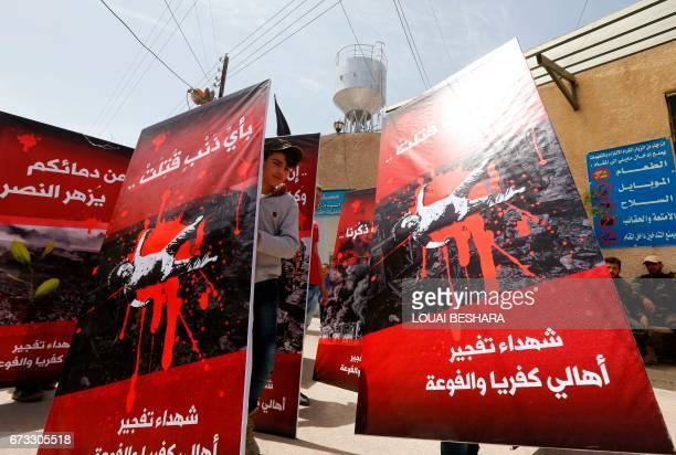 Children hold posters during a funeral ceremony in the Sayyida Zeinab mosque on the outskirts of Damascus on April 26 for the victims of a bombing...