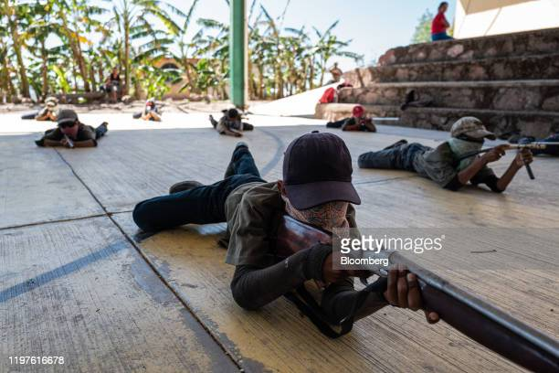 Children hold rifles and mock rifles during a Regional Coordinator of Community Authorities community police force gun training presentation held due...