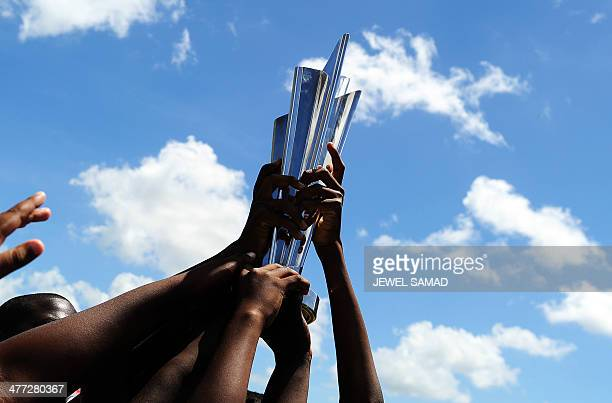 Children hold the ICC T20 World Cup trophy at the Kensington Oval in Bridgetown on March 8 2014 West Indies will play the threematch Twenty20 series...
