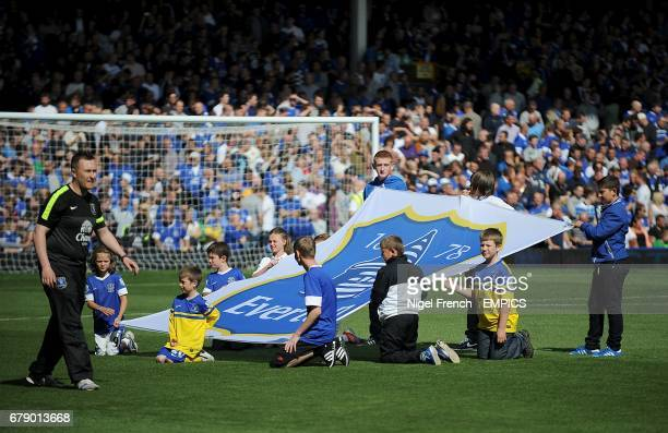 Children hold up a banner of the Everton club crest at Goodison Park