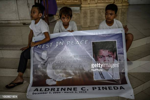 Children hold up a tarpaulin of 13yearold Aldrin Pineda who was shot to death by a police officer during his funeral in Manila Philippines March 14...