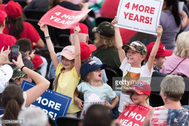 Children hold up campaign signs waiting for the arrival of President Donald Trump before a campaign rally at Smith Reynolds Airport on September 8,...