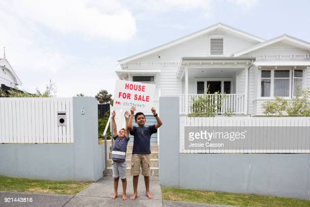 Children hold up for sale sign outside their house