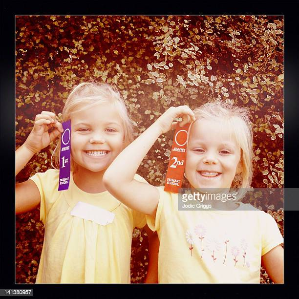 Children holding 1st and 2nd ribbons for athletics