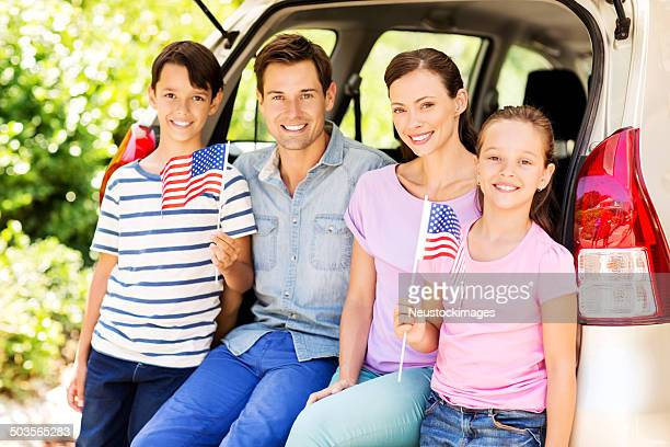 Children Holding American Flags With Parents In Car Trunk
