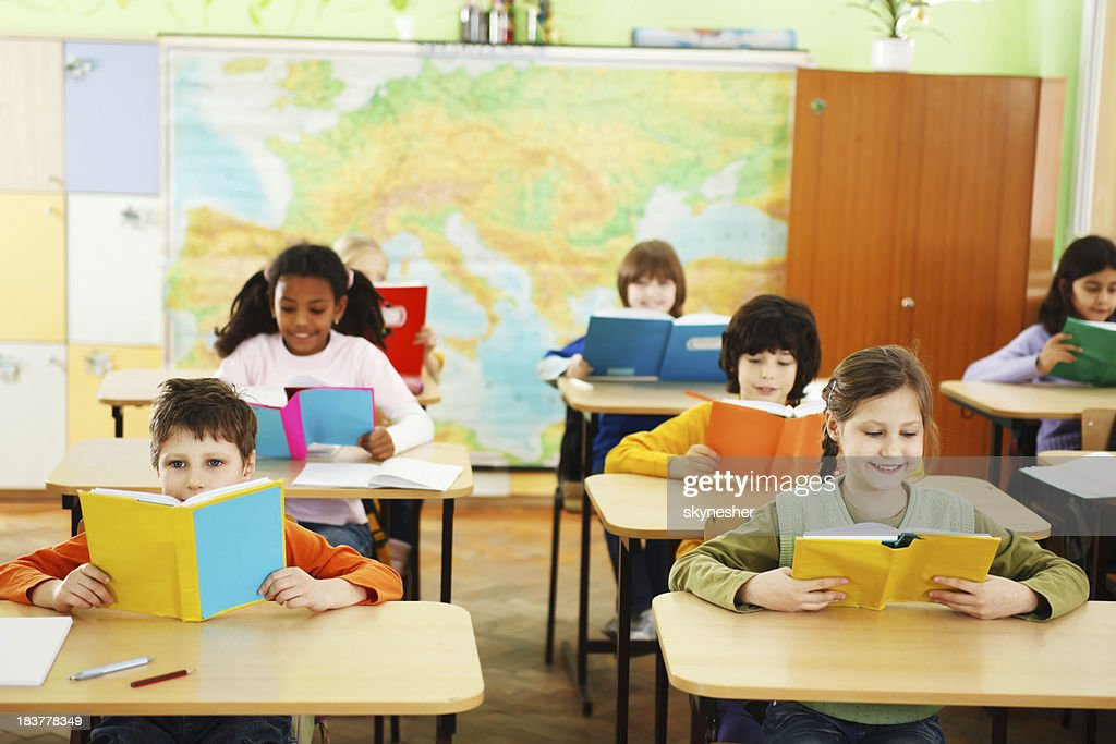 Children holding and reading textbooks in the classroom. : Stock Photo