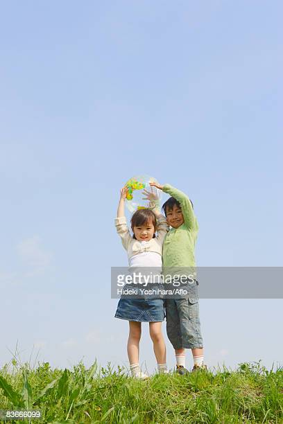 children holding ball in park against blue sky - 姉妹 ストックフォトと画像