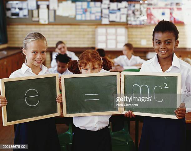 Children (8-10) holding blackboards displaying equation, portrait