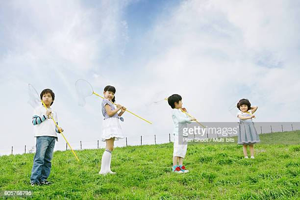Children (4-11) holding butterfly nets in meadow, low angle view