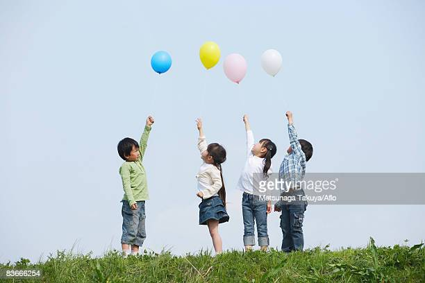 Children holding colorful balloons in park
