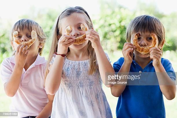 Children holding croissants to faces