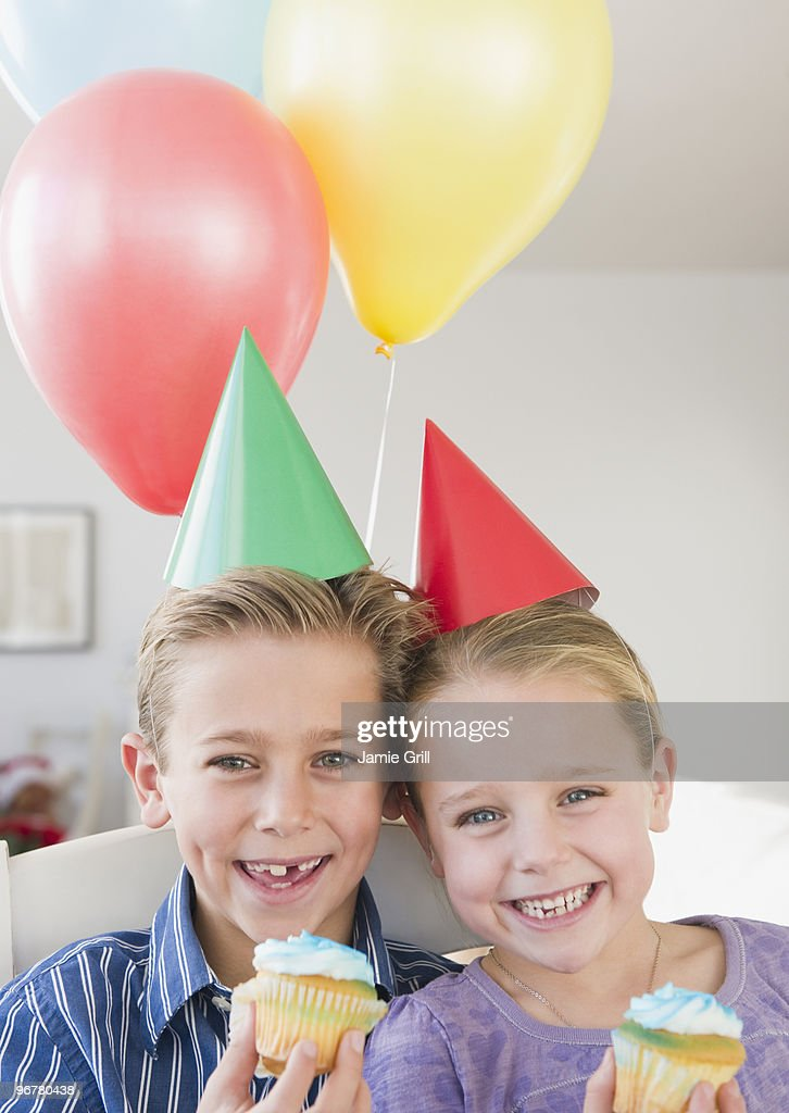 Children holding cupcakes at birthday party : Stock Photo