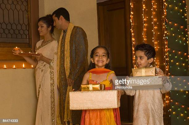 Children holding gifts with their parents holding religious offering in the background
