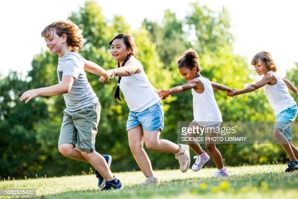 children holding hands and running - 鬼ごっこ ストックフォトと画像