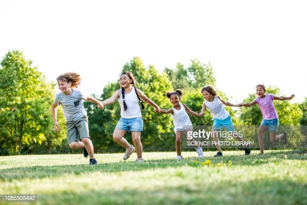 children holding hands and running - kids playing tag stock photos and pictures