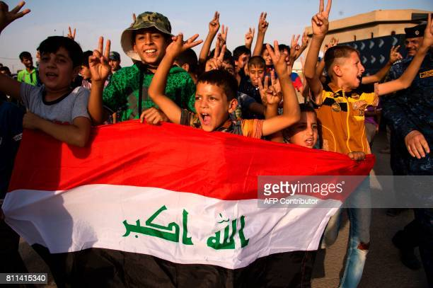 children holding Iraq's national flag react as Iraqi forces celebrate in the Old City of Mosul on July 9 2017 after the government's announcement of...