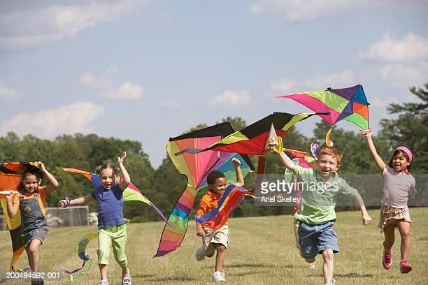 children holding kites above head, running outdoors - somente crianças imagens e fotografias de stock