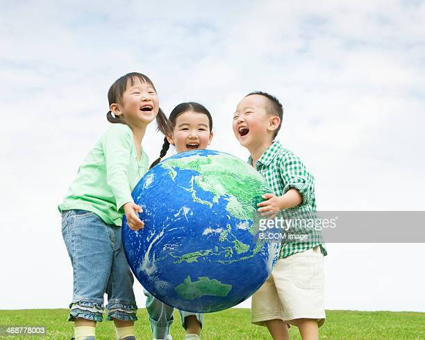 children holding planet earth - world kindness day stock photos and pictures