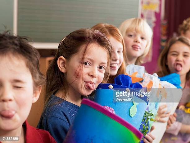 Children (4-7) holding school cone, sticking out tongue