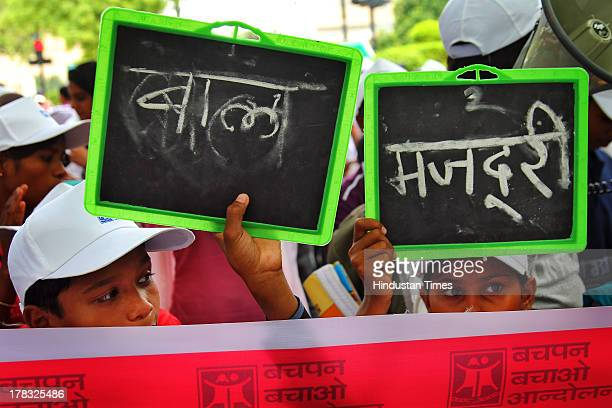 Children holding slates with 'Bal Majdori' written on them during protest against child labour and right for the proper literacy organised by Bachpan...