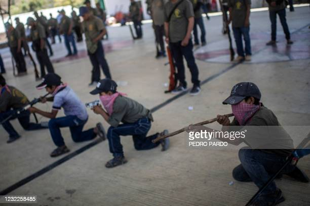 Children holding toy weapons and wooden sticks, take part in a training demonstration of the Regional Coordinator of Community Authorities vigilante...