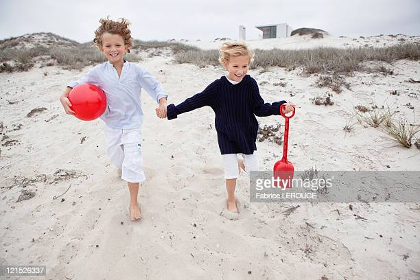 Children holding toys and running on sand