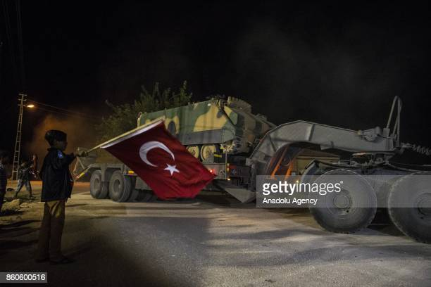 Children holding Turkish flags gather to show their support to soldiers as Turkish Army's armoured vehicles are deployed to the Reyhanli border due...