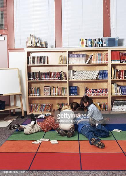Children (5-7) huddled together in library