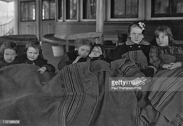 Children huddled under blankets between lessons at a tuberculosis school circa 1915