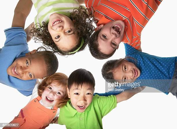 children hugging in a circle - multiculturalismo foto e immagini stock