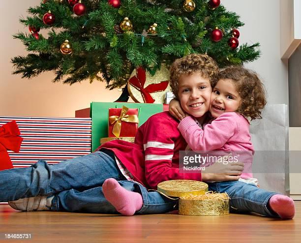 Crianças Agarrar na frente da Árvore de Natal