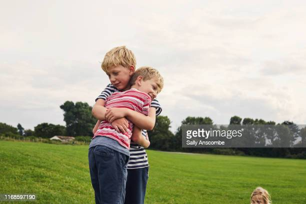 children hugging - sally anscombe stock pictures, royalty-free photos & images