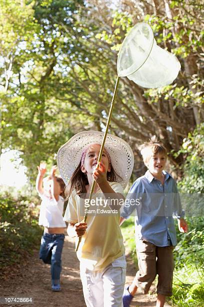 children hunting with butterfly net - innocence stock pictures, royalty-free photos & images