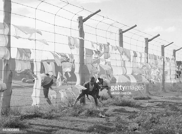 SOUTH AFRICA APARTHEID Children illegally crossing a barbedwire fence separating a black residential district from a white district during the rule...
