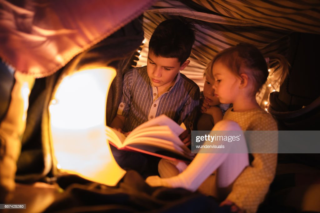 Children in a fort listening to a night story : Stock Photo
