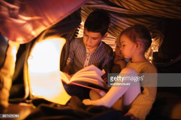 children in a fort listening to a night story - fortress stock pictures, royalty-free photos & images