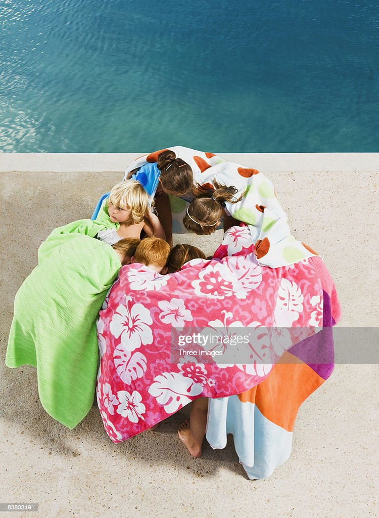 Children in a huddle by pool : Stock Photo