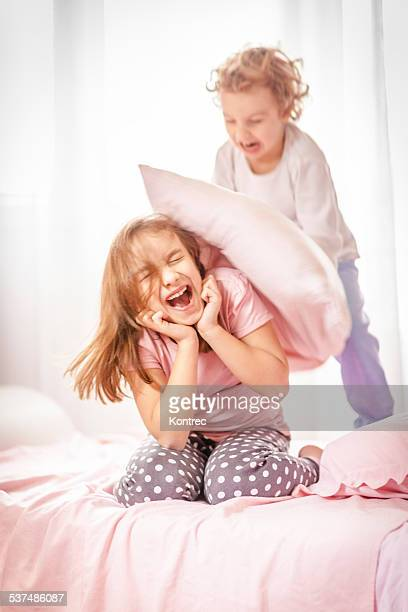 children in a pillow fight - girl fight stock photos and pictures